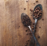 Image of spoons full of black peppercorn and allspice on wooden cutting board Royalty Free Stock Images
