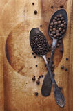 Image of spoons full of black peppercorn and allspice on wooden Royalty Free Stock Photo