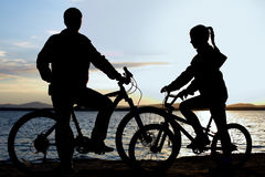 Image of sporty family on bicycles outdoors against sunset. Silhouette Stock Photography