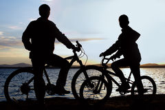 Image of sporty family on bicycles outdoors against sunset. Silhouette Stock Photo