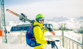 Image of sporty man in helmet with skis on his shoulder against background of snow-capped funicular. During day Royalty Free Stock Image