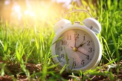 Image of spring Time Change. Summer back concept. Vintage alarm Clock outdoors.