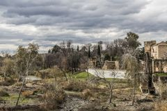 image of a stream between an arid ground with dry trees next to the ruins of the water mill of Albolafia stock photos