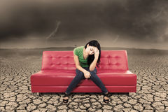 An image of stress female on sofa and dry ground Stock Photo