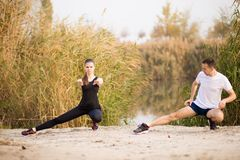 Image of strong fitness sport loving couple friends in park outd. Oors make stretching exercises royalty free stock image