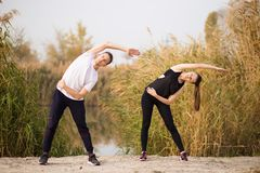Image of strong fitness sport loving couple friends in park outd. Oors make stretching exercises stock images