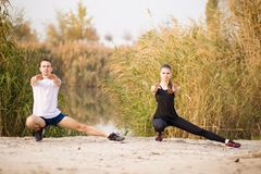 Image of strong fitness sport loving couple friends in park outd. Oors make stretching exercises stock photo