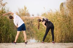 Image of strong fitness sport loving couple friends in park outd. Oors make stretching exercises stock image