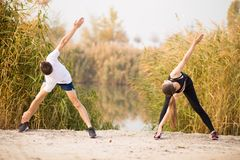 Image of strong fitness sport loving couple friends in park outd. Oors make stretching exercises stock photos
