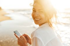 Image of stunning girl 20s smiling and using mobile phone, while walking by seaside. Image of stunning girl 20s smiling and using mobile phone while walking by royalty free stock images