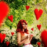 The image in the style of fantasy Valentine's Day. Young beautiful girl knits red hearts that fly around it. Royalty Free Stock Photos