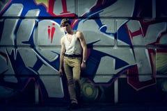 Image stylisée du type de mode contre un mur avec le graffiti Image libre de droits