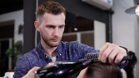 Image of stylish male barber using hairdryer for making modern haircut in barbershop. Young man is blowing dry client`s. Image of stylish male barber dressed in stock video