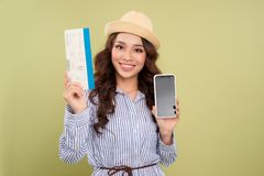 Image of successful voyage girl 20s expressing delight while holding air tickets and smartphone in hands isolated over green back stock images