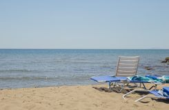 Image of sun lounger and white plastic chair on the beach with s Royalty Free Stock Photography