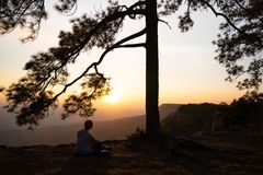 Image of sunrise or sunset on orange and yellow horizon with people`s silhouette surrounded by pine trees. Phu kradueng Thailand stock photography