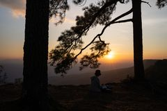 Image of sunrise or sunset on orange and yellow horizon with people`s silhouette surrounded by pine trees. Phu kradueng Thailand stock image