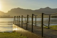 Image of the sunset at Rodrigo de Freitas lagoon in Rio de Janeiro. With its mountains, pier and characteristic outline Royalty Free Stock Images