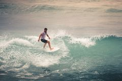 Surfer on Blue Ocean Wave, Bali, Indonesia. Riding in tube. Royalty Free Stock Photography