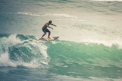 Surfer on Blue Ocean Wave, Bali, Indonesia. Riding in tube. Royalty Free Stock Image