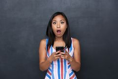 Image of surprised asian woman 30s using black cell phone royalty free stock photo