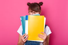 Image of surprised emotive european woman hides behind colourful paper folders, wears round black glasses, white t shirt, denim. Overalls, stands against pink stock photo