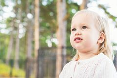 Image of sweet overweight baby girl looking away from camera. Close up portrait of a child. Cute toddler portrait. Image of sweet overweight baby girl looking stock photo