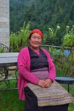 Elderly Sherpa woman who works in a local hostel in traditional attire sitting in the home garden