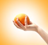 Image of a tasty orange in a human hand Stock Photo