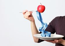 Tasty red apple and tape measure representing slimming and weight loss stock photography