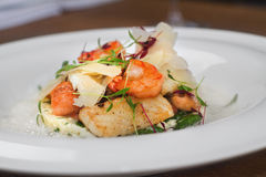 Image of tasty salad with shrimps and cheese in restaurant. Close image of salad with shrimps and chicken Stock Image