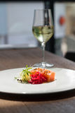 Image of tasty salmon on dish with white vine. Close image of salmon on dish in restaurant Stock Images