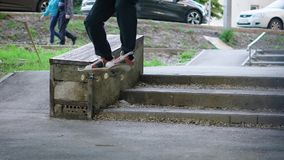 Image of teenager jumping up and doing boardslide on the ledge outdoors. Young man is riding skateboard on railing stock video footage