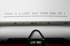 An Image of `there is a light that never goes out` written on a typewriter - Close up. Abstract Stock Photos
