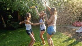Photo of three cheerful teenage girls dancing in the backyard garden udner garden water hose. Image of three cheerful teenage girls dancing in the backyard stock photo