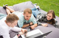 Three happy smiling young friends laying on a cushion outdoors a. Image of three happy smiling young friends laying on a big cushion or pillow and looking at royalty free stock photo