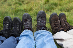 Image of three pairs of legs in hiking boots . Stock Photo