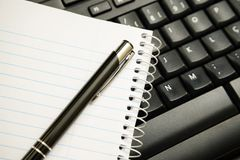 Pen and notebook on computer keyboard. Image to represent normal work in the office or at home royalty free stock photos