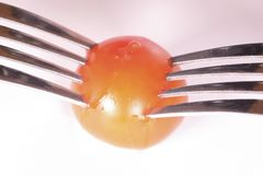 Tomato pinned on 2 forks. Image of a tomato pinned on 2 forks stock photography