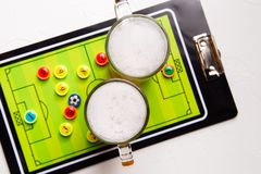 Image on top of two mugs of frothy beer, table football. On white table stock photography
