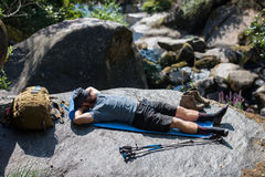 Tourist with a backpack resting lying on a rock Royalty Free Stock Photos