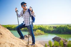 Image of tourist man with backpack with sticks for walking on hill. At summer day Royalty Free Stock Photo