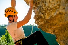 Image of tourist man in helmet clambering up. On cliff stock photo