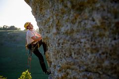 Image of tourist man in helmet clambering up. On cliff stock image