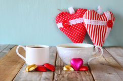 Image of tow red heart shape chocolates and couple cups of coffee on wooden table. valentine's day celebration concept Royalty Free Stock Image