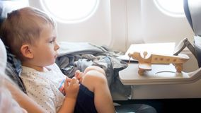 Image of toy wooden airplane on passenger seat of little boy stock photography