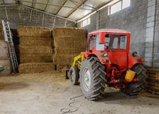 Tractor in a shed with haystacks. Image of tractor in a shed with haystacks Royalty Free Stock Image