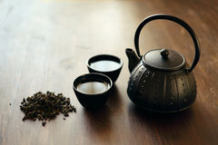 Image of traditional eastern teapot and teacups on wooden desk. Image of traditional eastern teapot and teacups on wooden table Royalty Free Stock Images