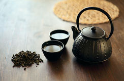 Image of traditional eastern teapot and teacups on wooden desk Stock Images