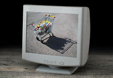 Image of a trolley with goods on a computer screen.  Royalty Free Stock Images